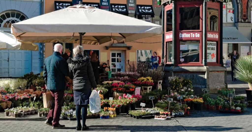 Ældre par udenfor en blomsterbutik på en solskinsdag