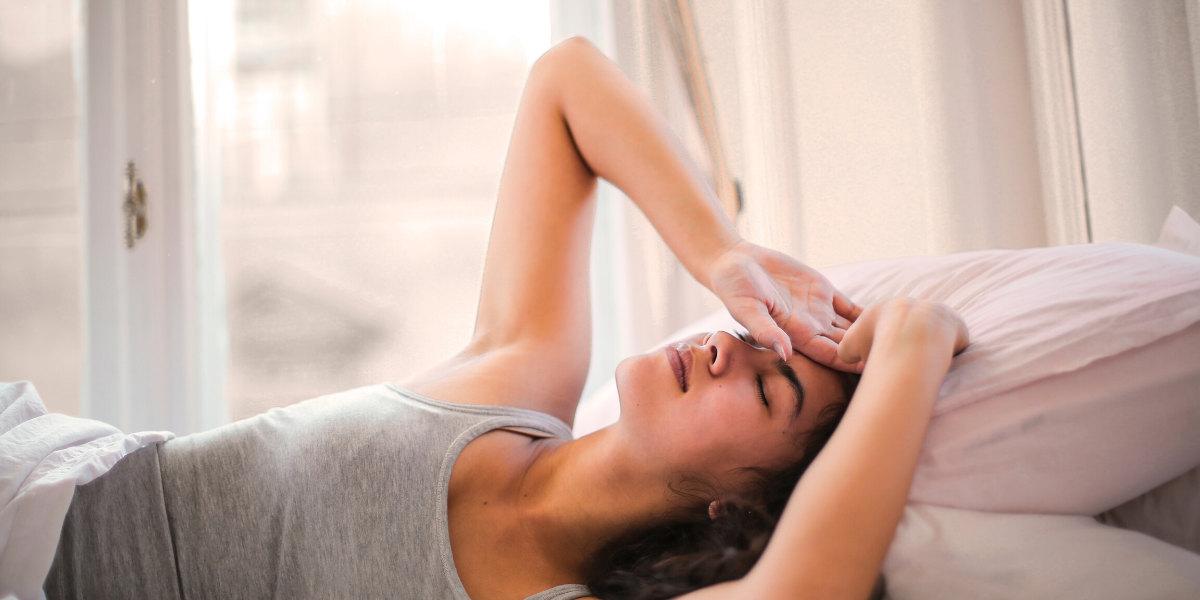 Kvinde med hovedpine ligger i sengen